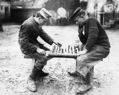 amid mud, two men play chess